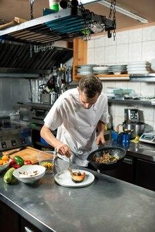 Młody mężczyzna szef kuchni w białym mundurze kładzie pieczone warzywa na kawałku smażonego łososia podczas przygotowywania smacznego posiłku dla klienta restauracji