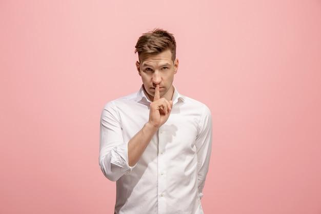 Młody mężczyzna szepcze sekret za jej ręką na różowym tle