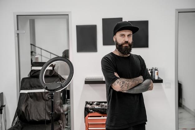 Młody mężczyzna tatuażysta z brodą, patrząc pozytywnie i szczęśliwie stojąc i uśmiechając się w miejscu warsztatu.