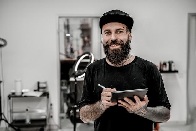 Młody mężczyzna tatuażysta z brodą, trzymając ołówek i szkic, patrząc pozytywnie i szczęśliwie stojąc i uśmiechając się w miejscu warsztatu.