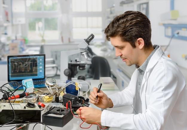 Młody mężczyzna technika lub inżynier naprawia sprzęt elektroniczny