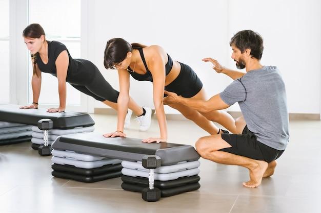 Młody mężczyzna trener osobisty pomagający kobiecie wykonującej pozę deski do jogi na zajęciach w jasnej, przestronnej siłowni w koncepcji zdrowia i sprawności lub zdrowego stylu życia