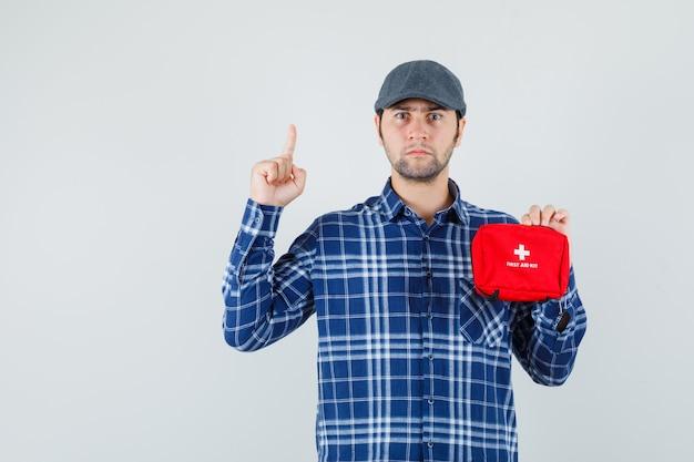 Młody mężczyzna trzyma apteczkę, skierowaną w górę w koszuli, czapce i patrząc poważny, przedni widok.