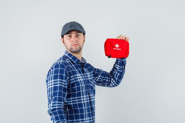Młody mężczyzna trzyma apteczkę w koszuli, czapce i wygląda niespokojnie. przedni widok.