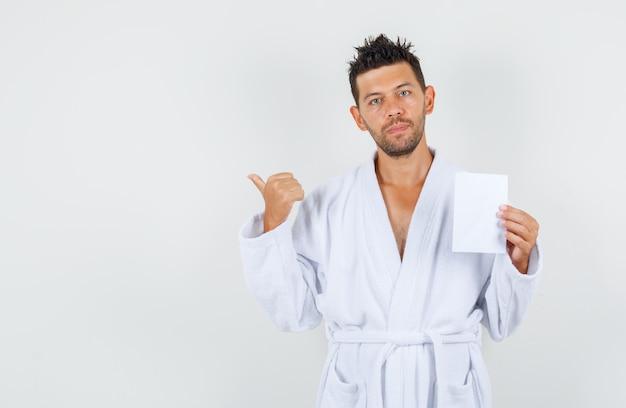 Młody mężczyzna trzyma arkusz papieru, wskazując z powrotem w białym szlafroku, widok z przodu.