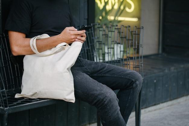 Młody mężczyzna trzyma białą eko torbę tekstylną na tle miejskiego miasta. pojęcie ekologii lub ochrony środowiska. biała eko torba do makiety.