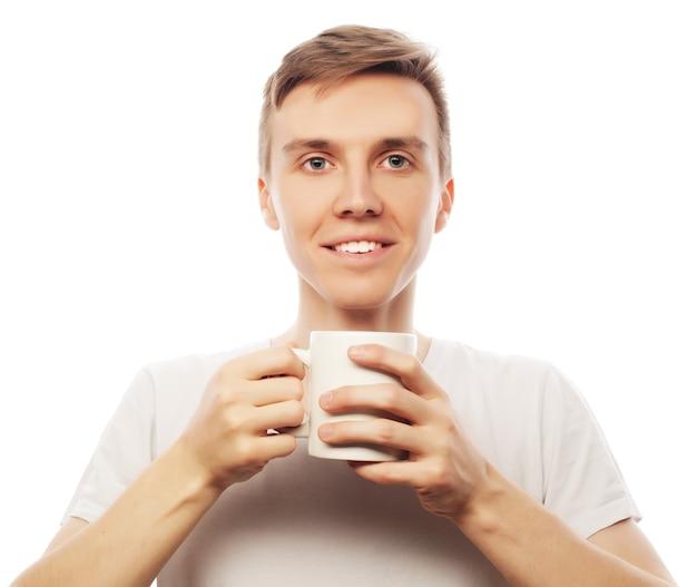 Młody mężczyzna trzyma białą filiżankę z kawą