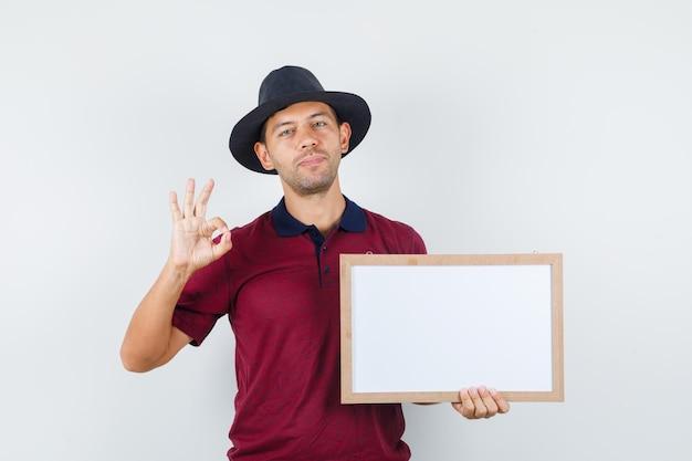 Młody mężczyzna trzyma białą tablicę z ok podpisać w t-shirt, kapelusz i wyglądający na zadowolony. przedni widok.