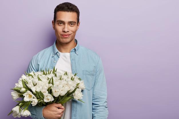 Młody mężczyzna trzyma bukiet białych kwiatów