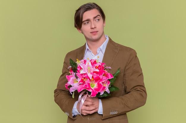 Młody mężczyzna trzyma bukiet kwiatów, uśmiechając się pewnie i gratulując międzynarodowego dnia kobiet stojącego nad zieloną ścianą