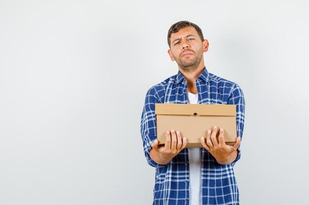 Młody mężczyzna trzyma ciężki karton w koszuli, widok z przodu.