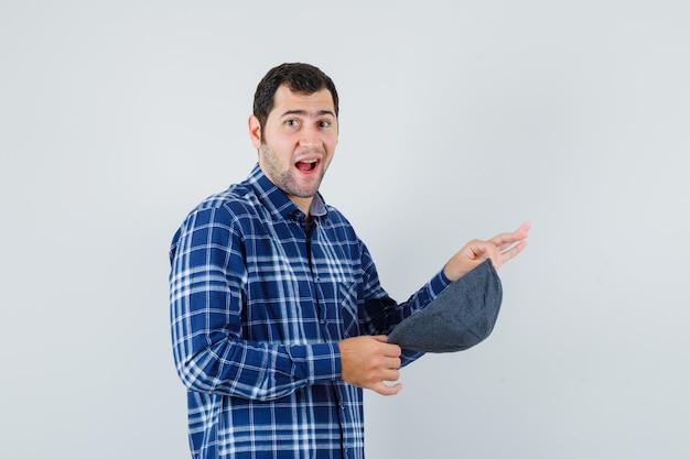 Młody mężczyzna trzyma czapkę w niebieskiej koszuli i wygląda zadowolony. przedni widok.