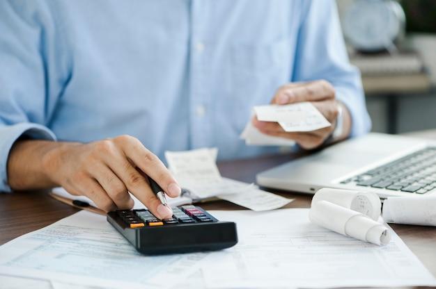 Młody mężczyzna trzyma długopis pracujący na kalkulatorze do obliczania płatności podatków od danych biznesowych