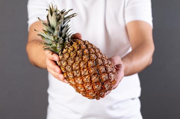 Młody mężczyzna trzyma dojrzałego i soczystego ananasa na białym tle