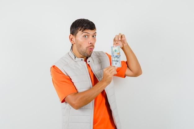 Młody mężczyzna trzyma dolara w t-shirt, kurtkę i patrząc zdumiony, widok z przodu.
