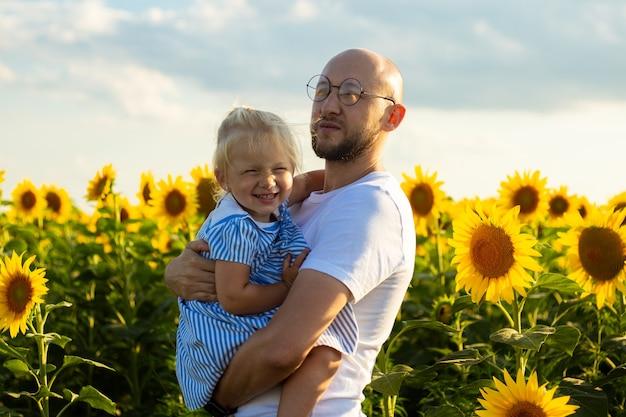 Młody mężczyzna trzyma dziecko w ramionach na słonecznikowym polu.