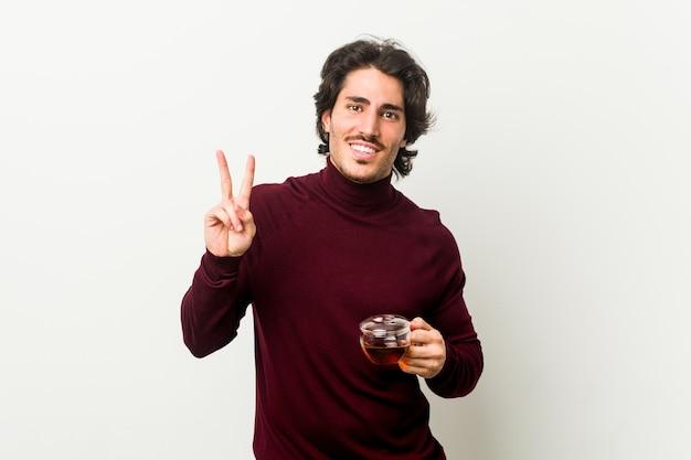 Młody mężczyzna trzyma filiżankę herbaty, pokazując numer dwa palcami.