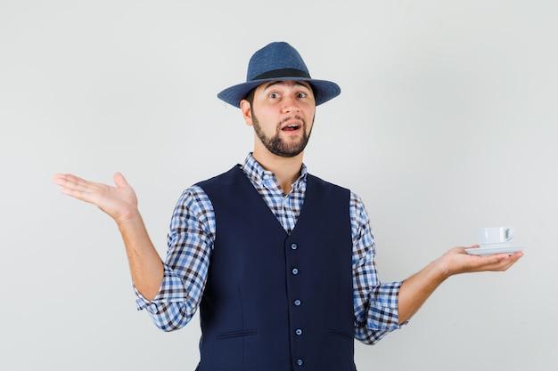 Młody mężczyzna trzyma filiżankę herbaty, rozkładając dłoń w koszuli, kamizelce, kapeluszu i wygląda pozytywnie. przedni widok.