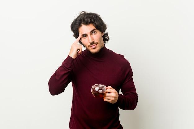 Młody mężczyzna trzyma filiżankę herbaty, wskazując palcem na świątynię, myśląc, skupiony na zadaniu.