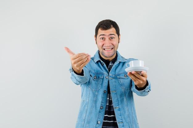 Młody mężczyzna trzyma filiżankę herbaty, zachęcając do przyjścia w t-shirt, kurtkę i wyglądający wesoło