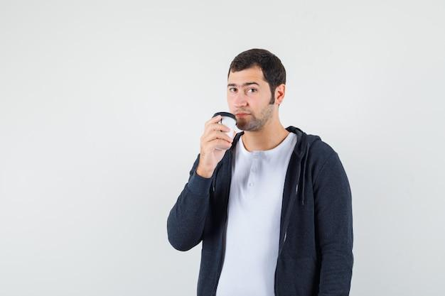Młody mężczyzna trzyma filiżankę kawy na wynos w białej koszulce i czarnej bluzie z kapturem na suwak i wygląda poważnie, widok z przodu.