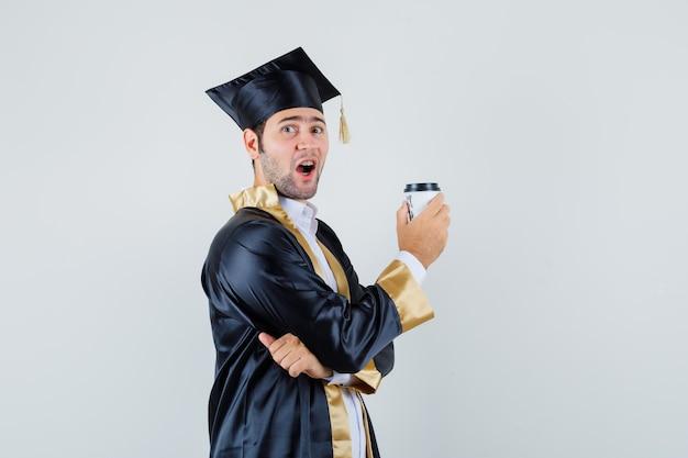 Młody mężczyzna trzyma filiżankę kawy w mundurze absolwenta i szuka szczęśliwy. przedni widok.