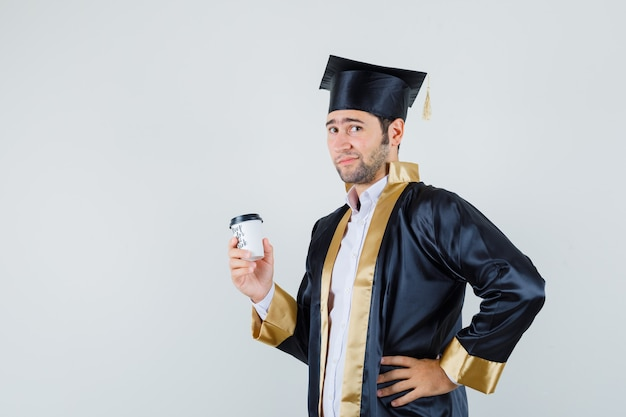 Młody mężczyzna trzyma filiżankę kawy w mundurze absolwenta i wygląda uroczo. przedni widok.