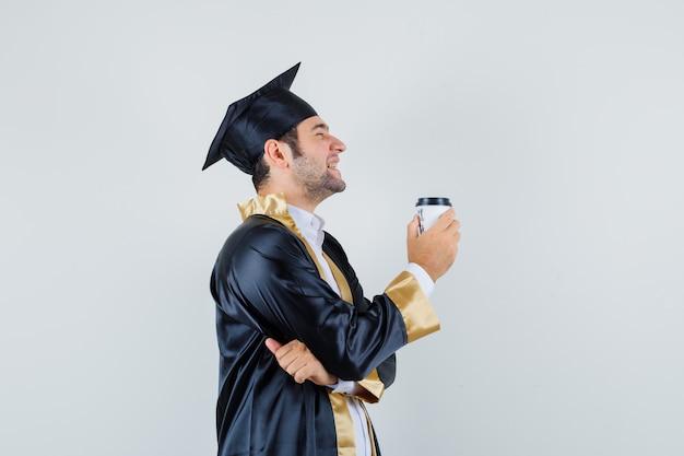 Młody mężczyzna trzyma filiżankę kawy w mundurze absolwenta i wygląda wesoło. .
