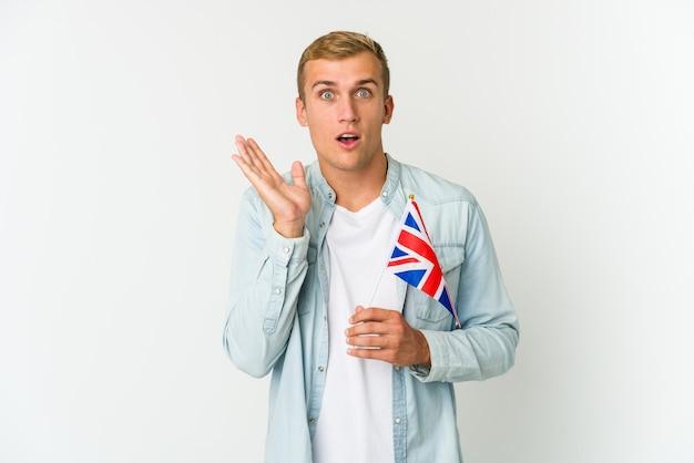 Młody mężczyzna trzyma flagę wielkiej brytanii na białym tle na białej ścianie zaskoczony i zszokowany