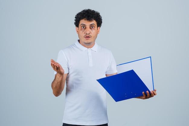 Młody mężczyzna trzyma folder i wyciąga rękę w kierunku kamery w białej koszulce i dżinsach i wygląda na zaskoczony, widok z przodu.