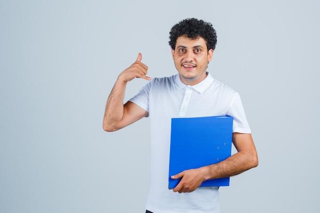 Młody mężczyzna trzyma folder plików i pokazuje gest zadzwoń do mnie w białej koszulce i dżinsach i wygląda poważnie, widok z przodu.