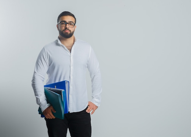 Młody mężczyzna trzyma foldery w białej koszuli, spodniach i wygląda pewnie