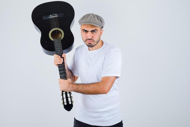 Młody mężczyzna trzyma gitarę w białej koszulce, czarnych spodniach, szarej czapce i wygląda na wściekłego