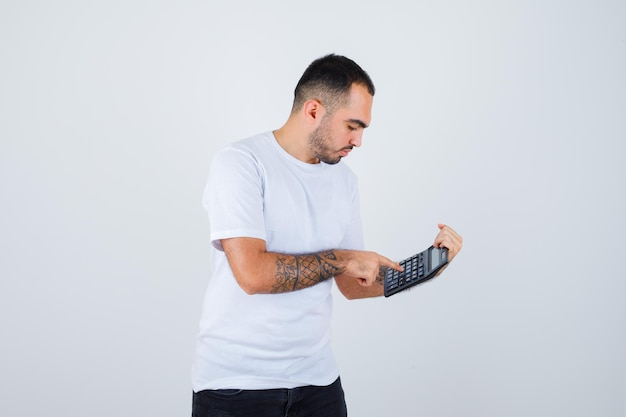 Młody mężczyzna trzyma kalkulator i robi na nim operacje w białej koszulce i czarnych spodniach i wygląda poważnie