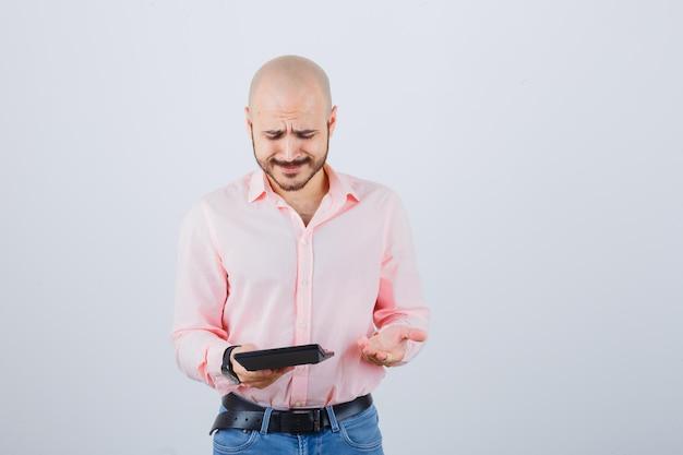 Młody mężczyzna trzyma kalkulator podczas rozmowy z gestem ręki w różowej koszuli, dżinsach, widok z przodu.