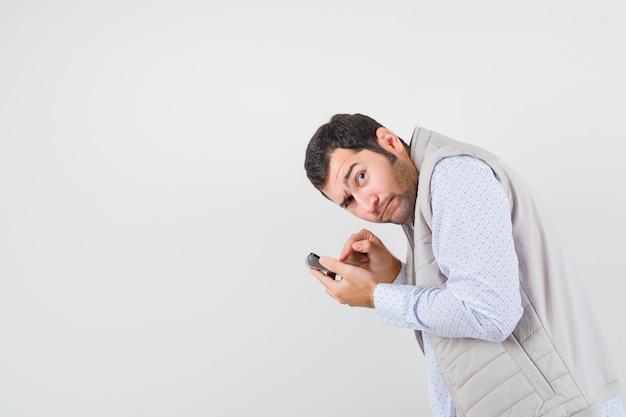 Młody mężczyzna trzyma kalkulator w jednej ręce i próbuje obliczyć w beżowej kurtce i czapce i wygląda na rozbawionego. przedni widok.