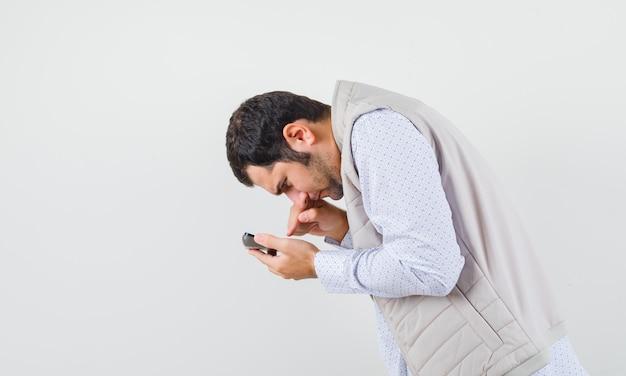 Młody mężczyzna trzyma kalkulator w jednej ręce i próbuje obliczyć w beżowej kurtce i czapce, patrząc skupiony. przedni widok.