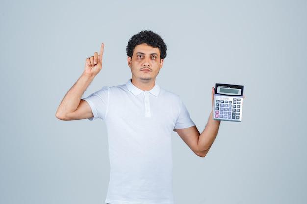 Młody mężczyzna trzyma kalkulator, wskazując w górę w białej koszulce i patrząc poważnie. przedni widok.