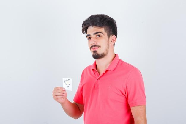 Młody mężczyzna trzyma karteczkę, odwracając wzrok w t-shirt i patrząc błogi, widok z przodu.
