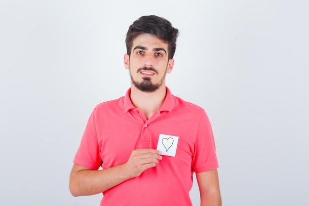 Młody mężczyzna trzyma karteczkę, odwracając wzrok w t-shirt i patrząc radosny, widok z przodu.