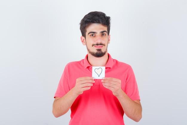 Młody mężczyzna trzyma karteczkę w t-shirt i wygląda ładny, widok z przodu.