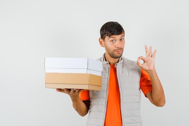 Młody mężczyzna trzyma kartony, pokazując ok gest w t-shirt, widok z przodu kurtki.