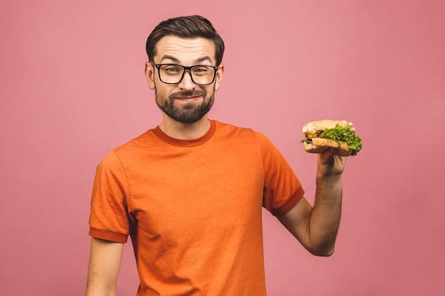 Młody mężczyzna trzyma kawałek hamburgera. student je fast food. bardzo głodny facet.