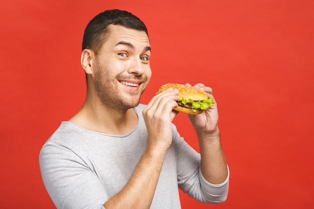 Młody mężczyzna trzyma kawałek hamburgera