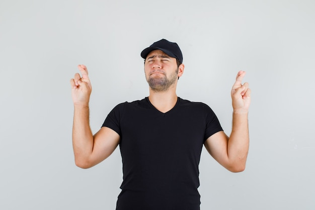 Młody mężczyzna trzyma kciuki w czarnej koszulce