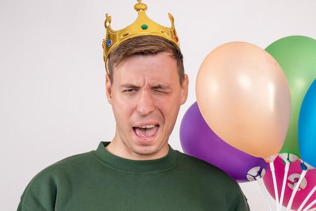 Młody mężczyzna trzyma kolorowe balony na białym tle