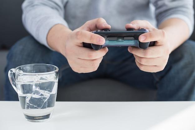 Młody mężczyzna trzyma kontroler gier grających w gry wideo