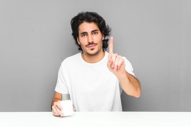 Młody mężczyzna trzyma krem po goleniu pokazuje numer jeden z palcem.