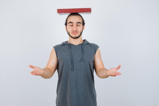 Młody mężczyzna trzyma książkę na głowie, udając, że trzyma coś w bluzie bez rękawów i wygląda na pewnego siebie. przedni widok.