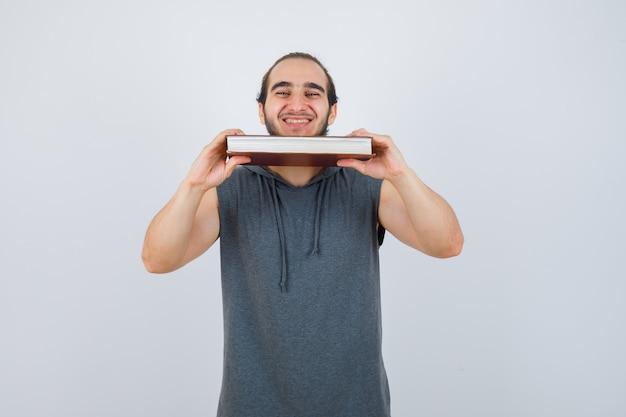 Młody mężczyzna trzyma książkę pod brodą w bluzie bez rękawów z kapturem i patrzy radośnie, widok z przodu.